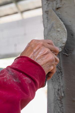steeplejack: builder worker plastering facade house building with putty knife float