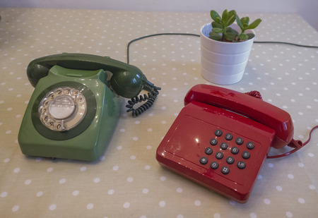 corded: Red and green corded landline telephone old fashioned with a cup or tee and a plant office working from home, homeworker, 2014