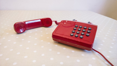 corded: Red corded landline telephone old fashioned with a cup or tee and a plant office working from home, homeworker, 2014 Stock Photo