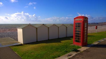 BT GPO red telephone box on a beach, public use call payphone Taken OCT 2014 on exmouth beach, devon, uk