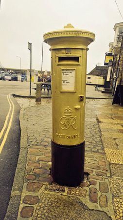buisiness: Gold postbox in reconition of Helen Glover winning an olympic medal in the 2012 London games, The first one to be painted gold in the UK, in Penzance Cornwall