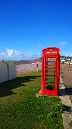 cast iron red: BT GPO red telephone box on a beach, public use call payphone Taken OCT 2014 on exmouth beach, devon, uk