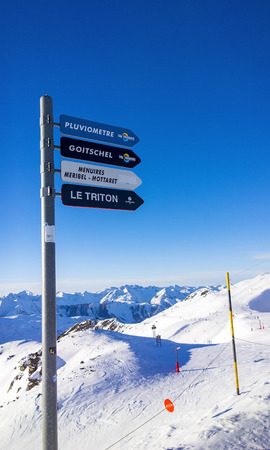 Val Thorens, France -  January  12, 2015: Showing one of the slopes at Val Thorens Ski Resort, with skiers heading along the slope and a sign.
