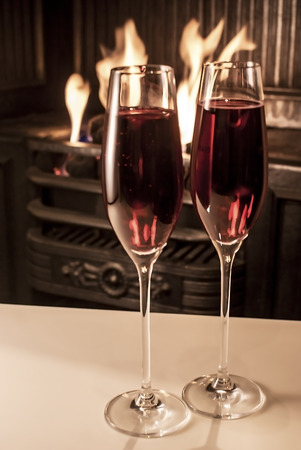 a stem here: 2 champagne glasses shown on a table next to a fireplace