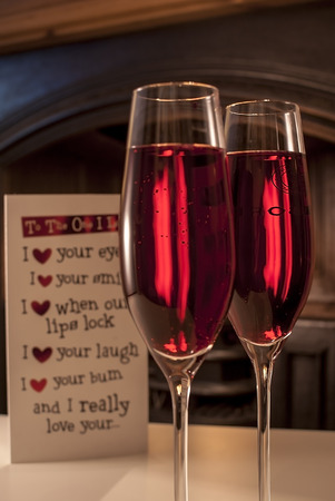 illustrative: Newton abbot, Devon, UK - January 28 2015, Showing 2 champagne glasses with rose wine next to a fireplace with a valentines card shown in the background, illustrative editorial
