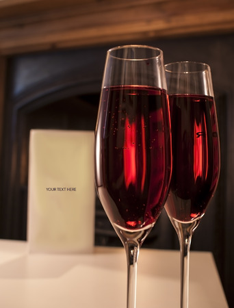 2 champagne glasses shown on a table next to a fireplace