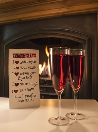 a stem here: Newton abbot, Devon, UK - January 28 2015, Showing 2 champagne glasses with rose wine next to a fireplace with a valentines card shown in the background, illustrative editorial
