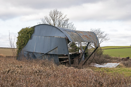 high winds: Ashburton, Devon UK - february 22 2015, Showing a collapsed corrigated iron barn as a result of high winds in the countryside. Stock Photo