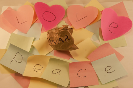 peice: Love and peace written on post it notes with a screwed up peice of paper with war written on it, symbolising, peace and love conquering war, some images with colour removed to certain sections