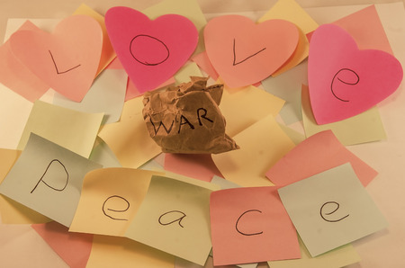 Love and peace written on post it notes with a screwed up peice of paper with war written on it, symbolising, peace and love conquering war, some images with colour removed to certain sections
