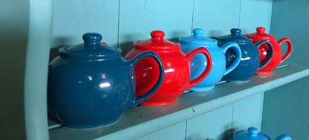 dresser: Red and blue tea pots on a dresser