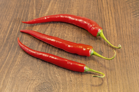 shown: Red Chilies shown lying on a wooden
