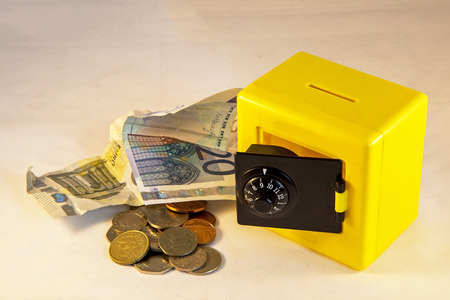 dosh: Plastic yellow safe isolated on a white background