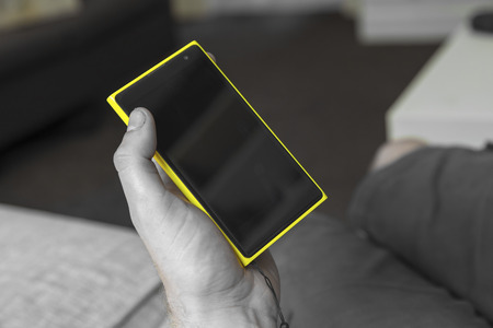 shown: Yellow smartphone shown in a hand .