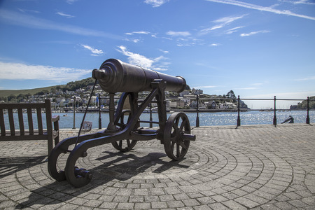 seaside town: Dartmouth Devon UK JUNE 4 2015  Showing an old cannon sat next to a seaside town Editorial