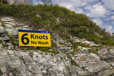 nautical vessels: Dartmouth, Devon, UK, JUNE 4 2015 - Showing a speed warning sign for nautical vessels