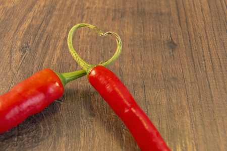 marrage: Showing 2 chillies with their stalks placed together to form a heart Stock Photo