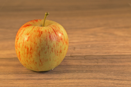 shown: Apple shown on a wooden .