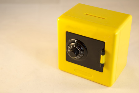monies: Plastic yellow safe isolated on a white  Stock Photo
