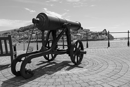 engineered: Dartmouth Devon UK JUNE 4 2015  Showing an old cannon sat next to a seaside town Editorial