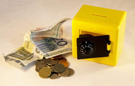 dosh: Plastic yellow safe isolated on a white  Stock Photo