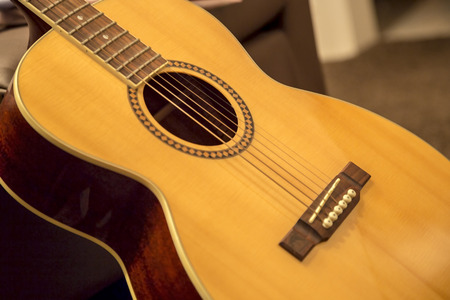 Showing a accoustic guitar resting against a sofa, Stock Photo