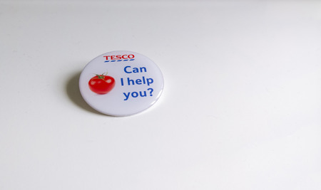 abbot: Newton abbot, Devon, UK, JUNE 8 2015 - Showing a tesco can i help you? badge lying on a white table
