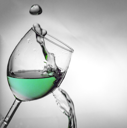 highlights: Fluid motion of coloured water in a wine glass with blownout highlights Stock Photo