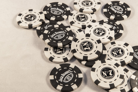 abbot: Newton abbot, Devon, UK, SEPTEMBER 9 2015 - Showing Jack Daniels brand poker chips laying on a white background. Editorial