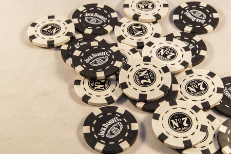 daniels: Newton abbot, Devon, UK, SEPTEMBER 9 2015 - Showing Jack Daniels brand poker chips laying on a white background. Editorial