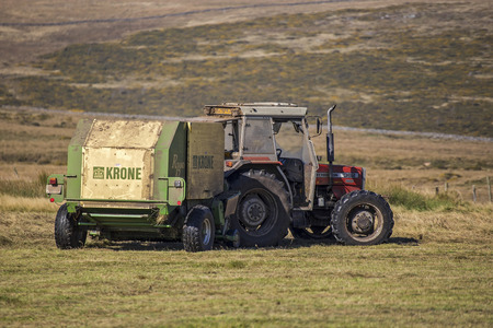 bailer: Postbridge, Devon, UK October 1 2015 - Showing a tractor, driver and round bailer, on a farm on the darmoor national park.