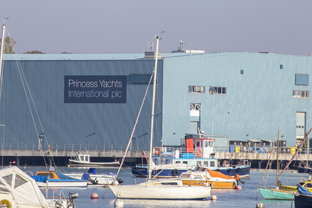 plc: Plymouth, Devon, UK October 3 2015 - Showing the Princess Yachts International plc, enginering warehouse located at the harbour in plymouth, with various dinghys and yacths shown in the foreground