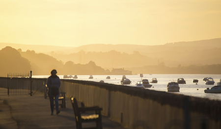 unrecognisable person: Hazy sunset along the teingmouth estuary during summer 2015, showing an unrecognisable person walking on the path Stock Photo