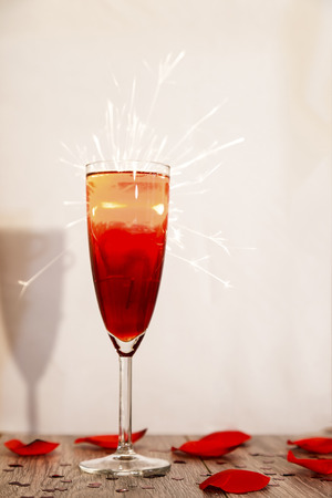 highlights: Showing a champagne glass with red wine and blown out highlights, with sparks coming from behind, with a shadow in clear sight