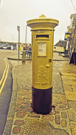 buisiness: Penzance, Cornwall, UK, Jan 21 2014 -  Showing a gold postbox in reconition of Helen Glover winning an olympic medal in the 2012 London games, The first one to be painted gold in the UK,