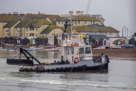dredging: Teignmouth, Devon, UK, November 04 2015 - Showing a dredging boat dredging the bottom of the entrance to the Teign estuary to keep the waterways at an appropriate depth and navigable.