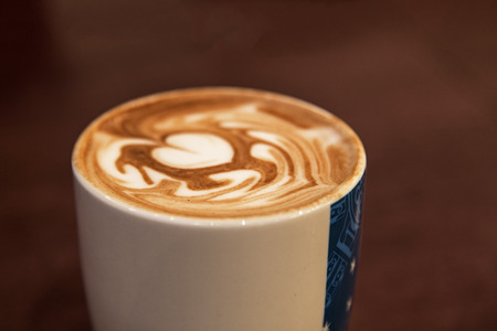 restuarant: Showing a leaf shape ontop of a hot chocolate drink in a restuarant,