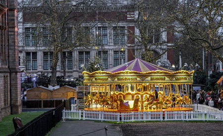 London, UK, 6 December 2015 - Showing a merry go round fair ride outside the national history museum, with a croud of people queueing to ride it, taken during christmas