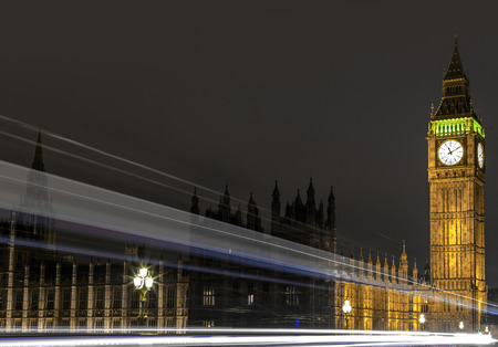 minuet: Westminster, London, UK, December 16 2015 - Showing Big Ben clock tower lite up at night with light streaks from a passing london bus, shot on a long exposure to creat light trails. Stock Photo