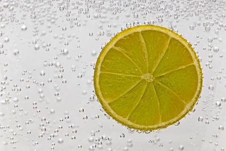 segmento: Que muestra un segmento de la fruta del lim�n en una bebida gaseosa Foto de archivo