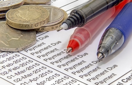 Showing a mortgage bill with pens and british coins