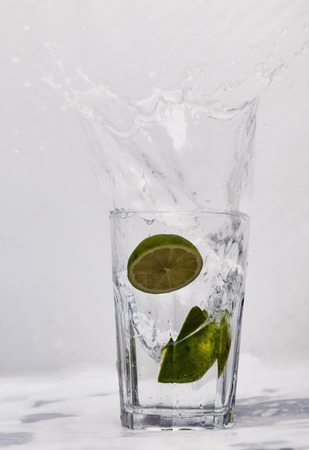 Showing a glass with a lime segment being dropped into it Stock Photo