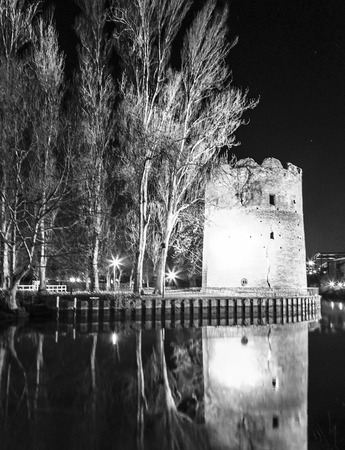 sullen: Norwich, Northfolk, UK, March 30th 2016 - Showing a round old structure beside the riverbank in Norwich city centre, with reflections from the river in black and white