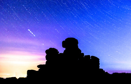 stary: Great Staple Tor on Dartmoor National Park in Devon UK, at night with star trails and a shooting star