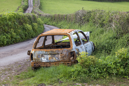 abbot: Newton abbot, Devon, UK,  May 3 2016 - Showing an old burnt out, vandalised and abandoned car left beside the side of a country lane in rural devon.
