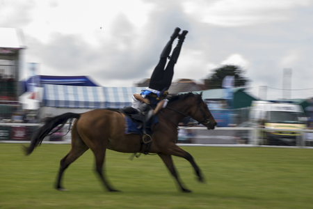 Wadebridge, Cornwall, UK, June 11 2016 - Showing horse riders, riding and doing several riding tricks with horses on green grass field at a local show.