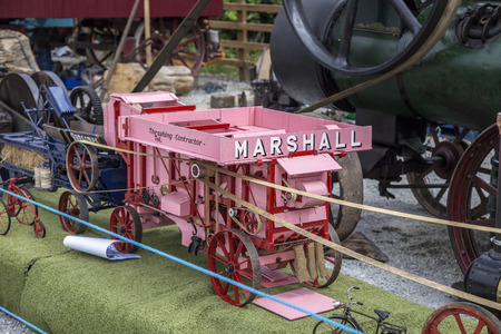 steam traction: Wadebridge, Cornwall, UK, June 11 2016 - Showing a model of an old retro marshall red agricultural bailer  machinary at a classice tractor show