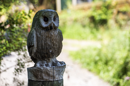 Ashburton, Devon, UK, July 6 2016 - Showing a wooden carved owl on a gate post at the entrance to an owl sanctuary