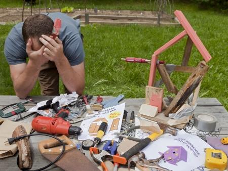 Een man is gefrustreerd en boos op het opbouwen van een slechte vogelhuisje Stockfoto