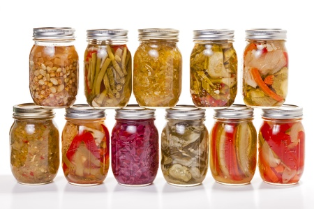 A collection of pickled and jarred vegatables in glass jars against a white background